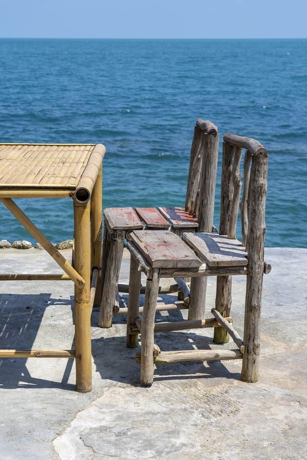Tabela de bambu e cadeiras de madeira no caf? vazio ao lado da ?gua do mar na praia tropical Ilha Koh Phangan, Tail?ndia fotografia de stock