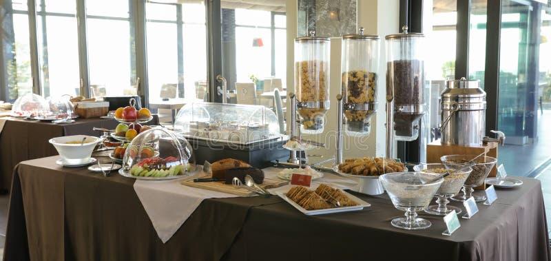 Tabela de bufete saudável do café da manhã dos vários frutos, iogurtes, flocos e da aveia a comer com leite, bolos durante férias imagem de stock royalty free