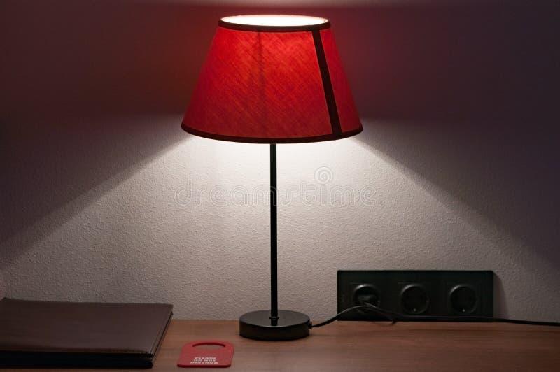 Tabela de cabeceira em que a mentira o dobrador de couro do menu, não perturba o sinal e a lâmpada com um abajur de matéria têxti imagem de stock