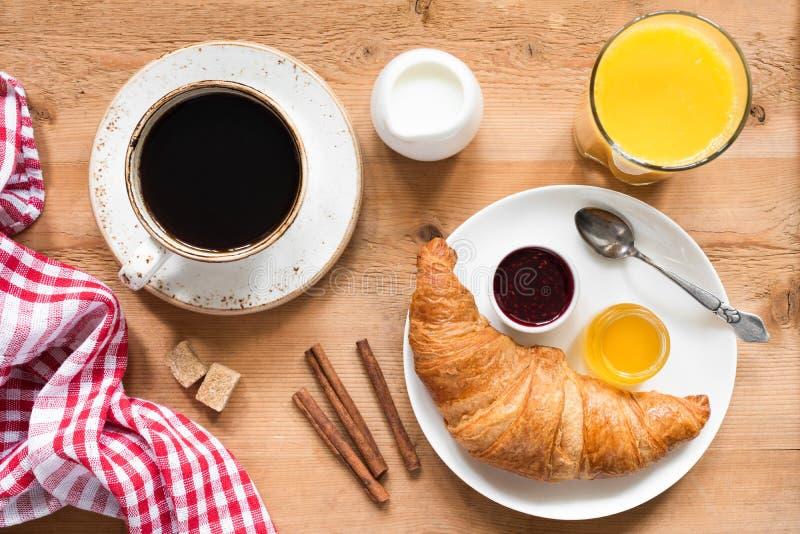 Tabela de café da manhã com croissant, café, suco de laranja e doce imagens de stock royalty free