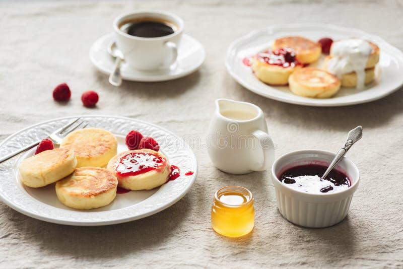Tabela de café da manhã com Curd Fritters ou panquecas, café, doce e mel imagem de stock