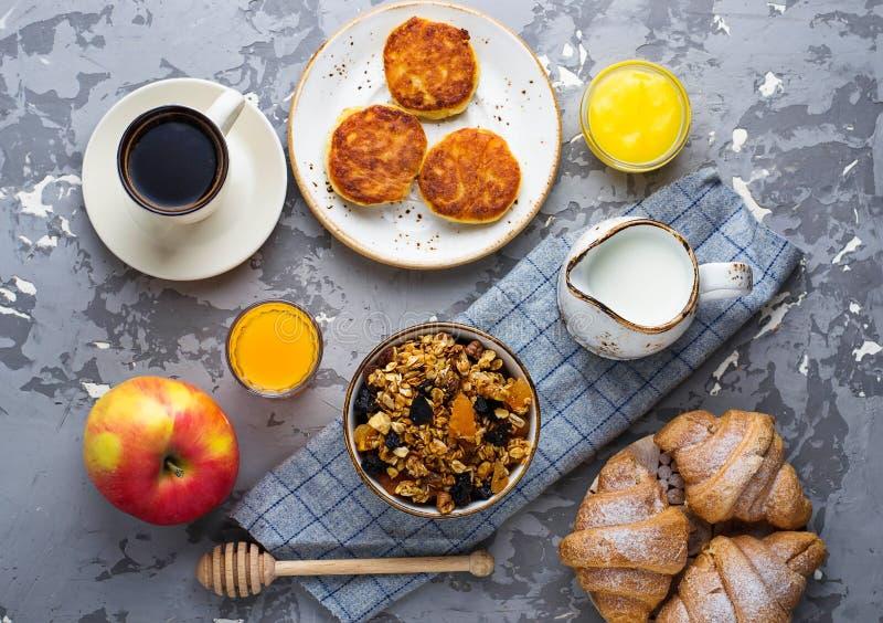 Tabela de café da manhã com granola, croissant, maçã, café, suco imagem de stock royalty free