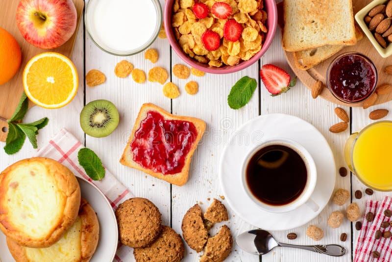 Tabela de café da manhã com os ingredientes saborosos saudáveis Café, brinde, doce, bolos de queijo, flocos de milho, cookies, am fotografia de stock
