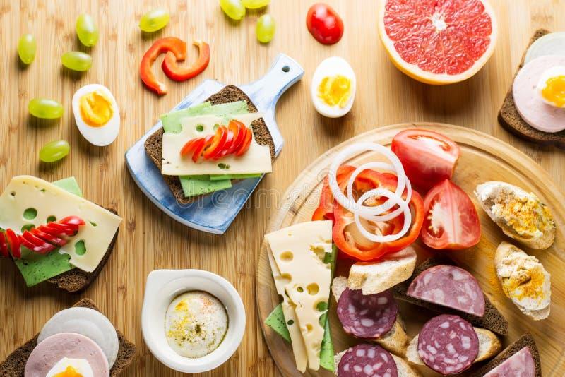 Tabela de café da manhã com sanduíches do queijo, salsicha, vegetais, os ovos cozidos duros e os frutos fotos de stock
