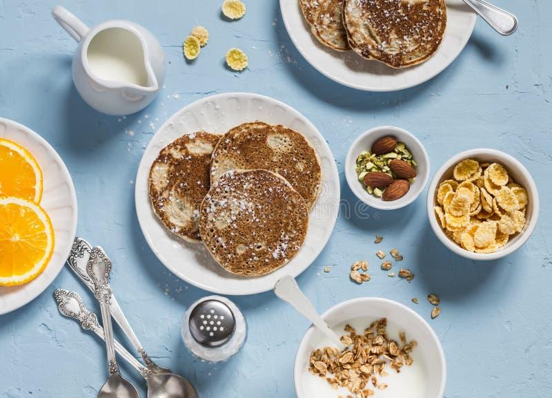 Tabela de café da manhã Panquecas inteiras do trigo, iogurte grego com granola caseiro, fatias alaranjadas, porcas, flocos de mil imagens de stock