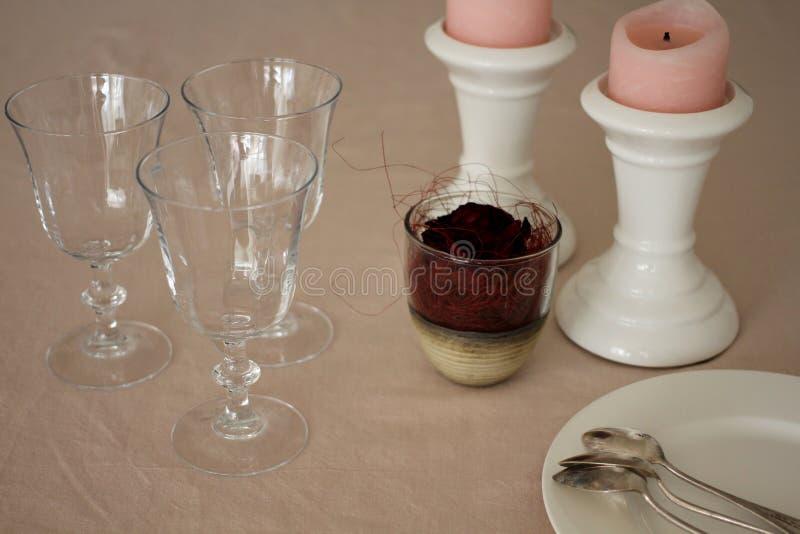 Tabela de domingo com vidros, cor-de-rosa românticos e velas imagem de stock royalty free