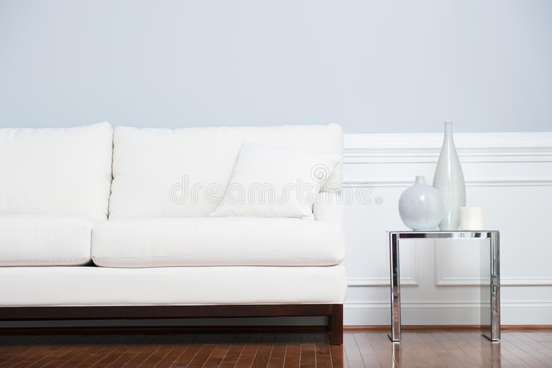 Tabela de extremidade branca do sofá e do vidro de encontro à parede azul fotografia de stock