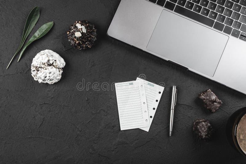 A tabela de funcionamento de um homem de negócios, o portátil e algum negócio notam etiquetas, tomam o café da manhã doces e café foto de stock