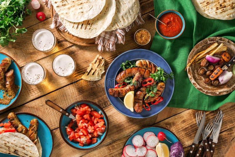 Tabela de jantar com salsicha, a tortilha, cerveja e o diferente grelhados imagens de stock royalty free