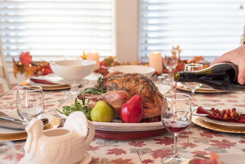 Tabela de jantar do feriado com peru roasted, vinho tinto de derramamento do homem no primeiro plano fotografia de stock royalty free