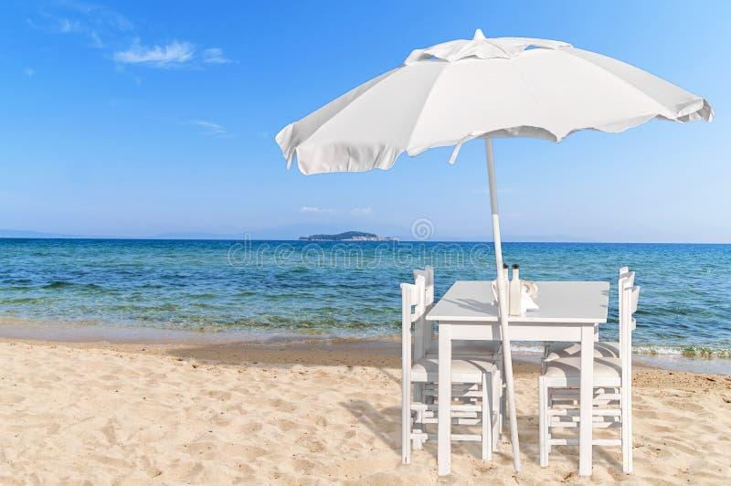 Tabela de madeira com a cadeira quatro no Sandy Beach bonito e em s azul imagens de stock royalty free