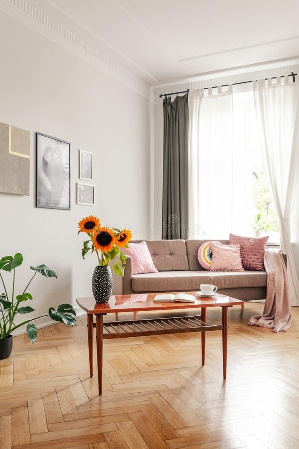 Tabela de madeira com os girassóis na frente do sofá no interior da sala de visitas com janela e cartazes Foto real fotografia de stock royalty free
