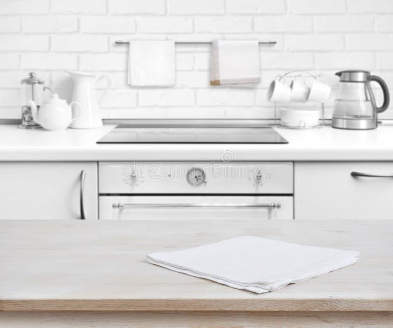 Tabela de madeira com a toalha sobre fundo rústico defocused do banco da cozinha foto de stock royalty free