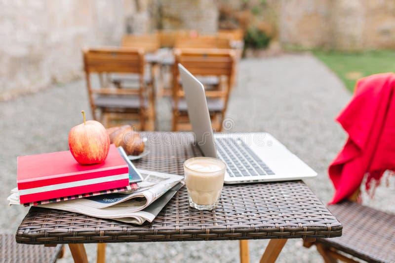 Tabela de madeira com um vidro da agitação de leite, do computador vermelho do maçã e o branco Jornais e livros ao lado do latte  fotografia de stock