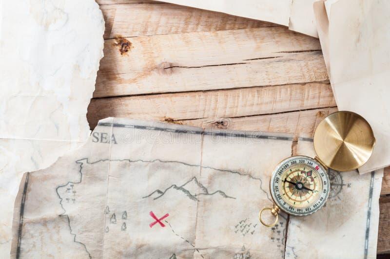 A tabela de madeira com vintage envelheceu o mapa de papel e antigo do tesouro com compasso Com espaço para seu projeto imagem de stock