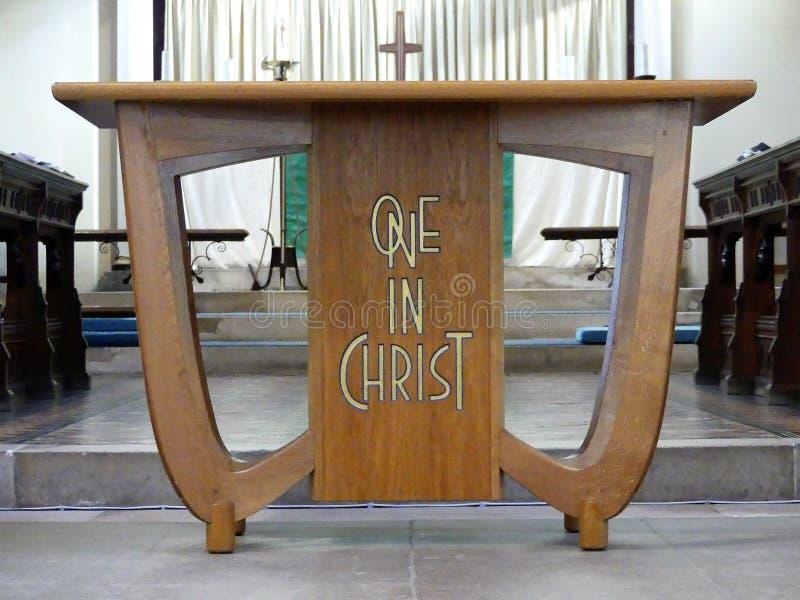 Tabela de madeira da igreja inscreida com as palavras uma em Cristo fotos de stock