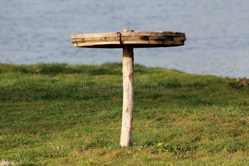 Tabela de madeira do círculo caseiro montada no único polo de madeira no meio da grama sem cortes do banco de rio local com o rio fotos de stock royalty free
