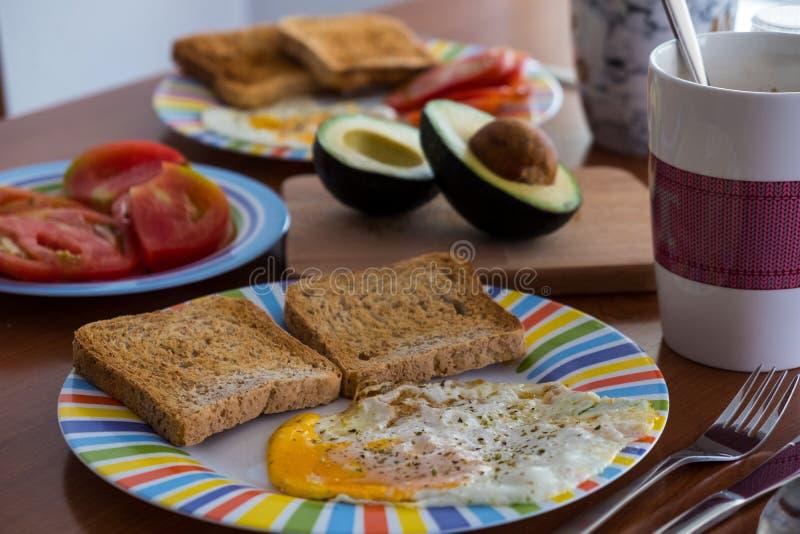 Tabela de madeira do café da manhã com fatia, ovo frito, tomate e abacate do pão fotografia de stock