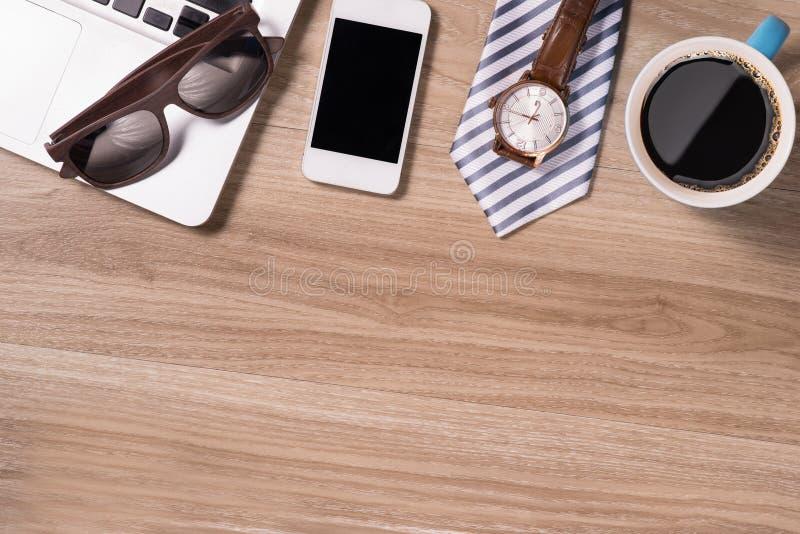 Tabela de madeira do escritório com o telefone do portátil e o copo de café espertos Vista superior fotos de stock royalty free