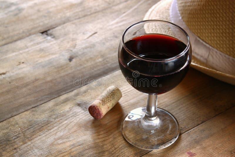 A tabela de madeira do vidro de vinho tinto no por do sol estourou a imagem filtrada vintage imagens de stock royalty free