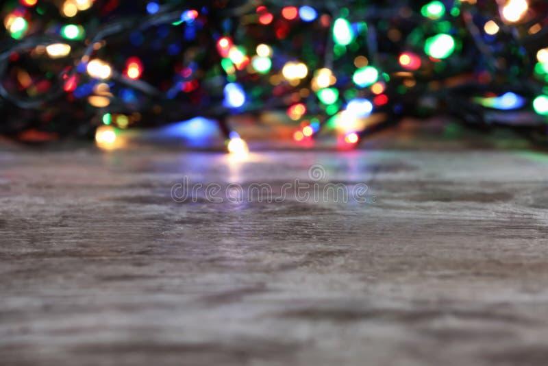 Tabela de madeira e luzes de Natal borradas foto de stock royalty free