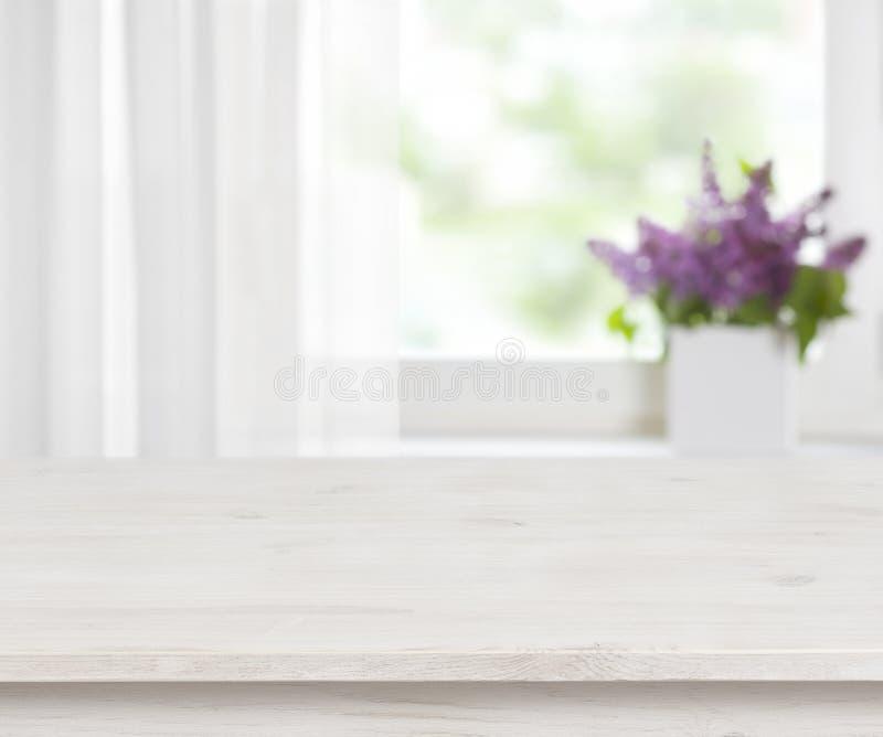 Tabela de madeira em janela defocused com fundo roxo do potenciômetro de flor fotografia de stock royalty free