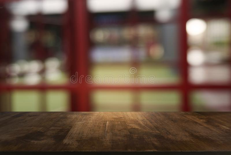 A tabela de madeira escura vazia na frente do sumário borrou o fundo fotos de stock
