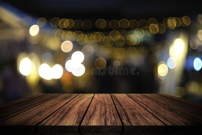 Tabela de madeira na frente da luz borrada sumário imagem de stock royalty free