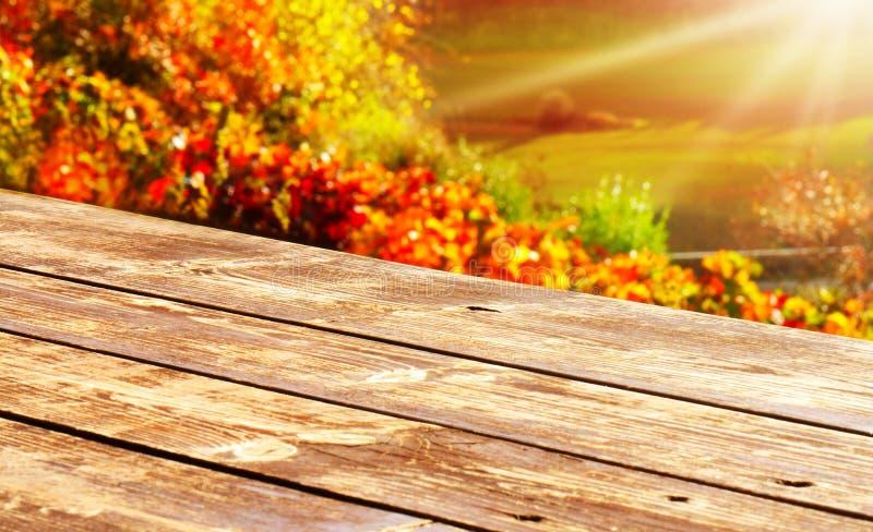 Tabela de madeira na frente das folhas de outono coloridas fotografia de stock royalty free