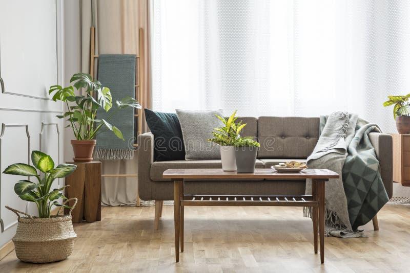 Tabela de madeira na frente do sofá bege no roo vivo brilhante simples fotos de stock royalty free