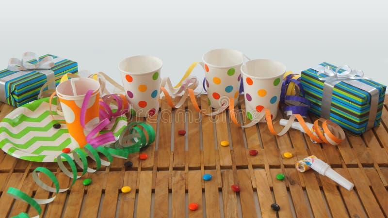 Tabela de madeira rústica com flâmulas coloridas, presentes, copos plásticos, placa plástica, doces no fundo branco fotos de stock royalty free