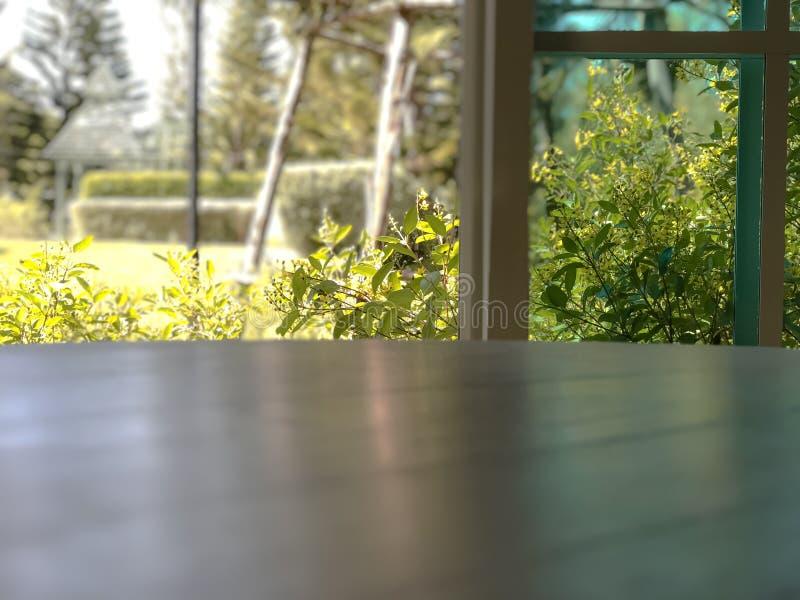 Tabela de madeira vazia com fundo borrado com janela e jardim imagens de stock royalty free