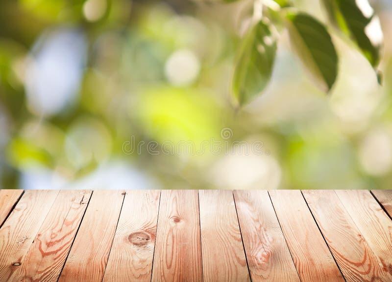 Tabela de madeira vazia com fundo do bokeh da folha. imagens de stock