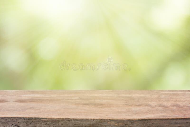 Tabela de madeira vazia com fundo do bokeh da luz solar foto de stock
