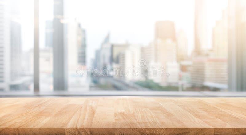 Tabela de madeira vazia com opinião do escritório da sala do borrão e da cidade da janela imagem de stock