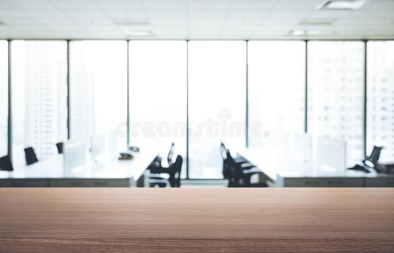 Tabela de madeira vazia com opinião do escritório da sala do borrão e da cidade da janela fotografia de stock royalty free