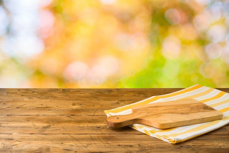 Tabela de madeira vazia com placa de corte e toalha de mesa sobre o fundo do parque natural do outono imagem de stock royalty free