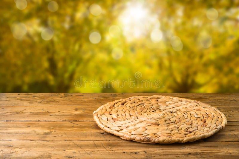 Tabela de madeira vazia com placemat redondo de vime sobre o fundo do parque natural do outono fotos de stock