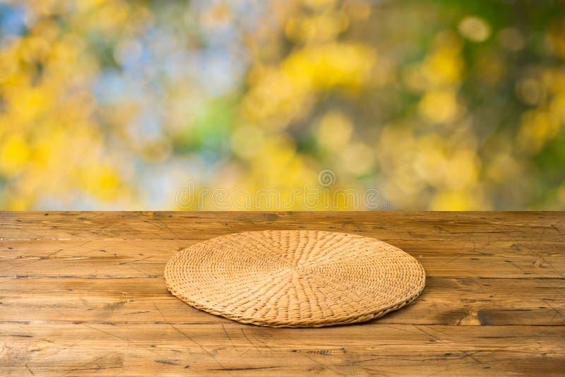 Tabela de madeira vazia com placemat redondo de vime sobre o fundo do parque natural do outono imagens de stock royalty free