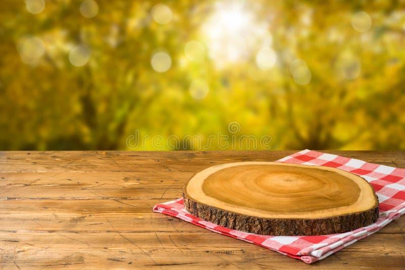Tabela de madeira vazia com toalha de mesa e placa de madeira sobre o fundo do parque natural do outono fotografia de stock royalty free