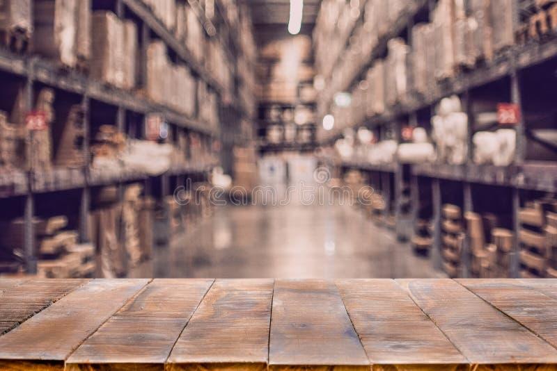 Tabela de madeira vazia em caixas borradas defocused em fileiras das prateleiras fotos de stock