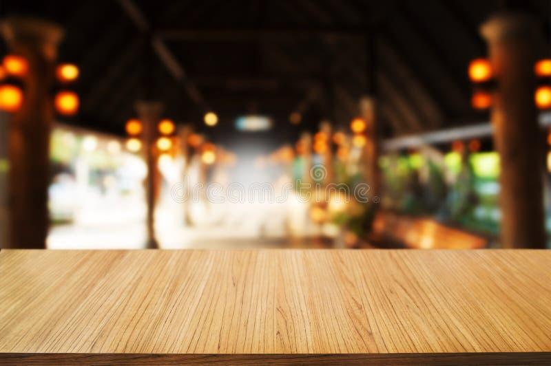 tabela de madeira vazia na frente do fundo do sumário da montagem do borrão imagem de stock