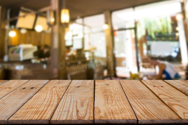 tabela de madeira vazia na frente do fundo do sumário da montagem do borrão fotografia de stock