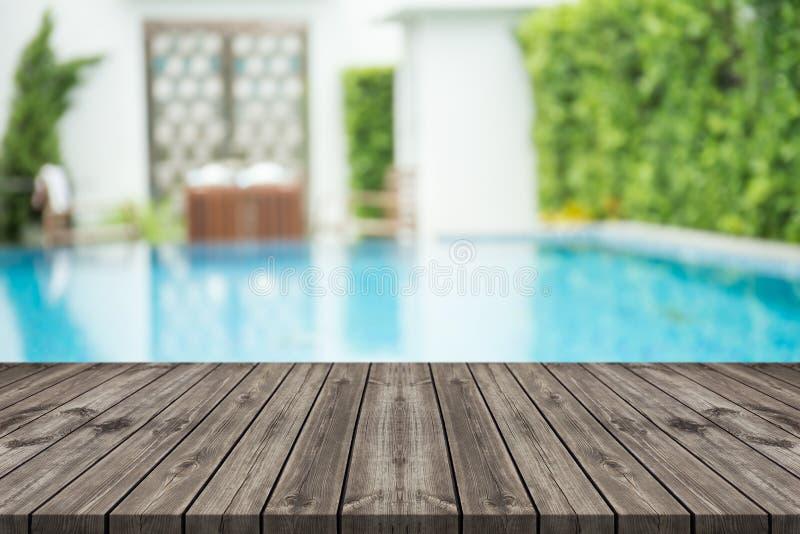 Tabela de madeira vazia na parte dianteira com fundo borrado da piscina fotografia de stock royalty free
