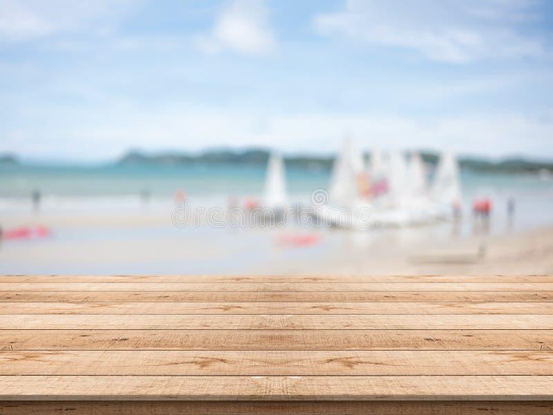 Tabela de madeira vazia na parte dianteira com fundo borrado na praia imagens de stock royalty free