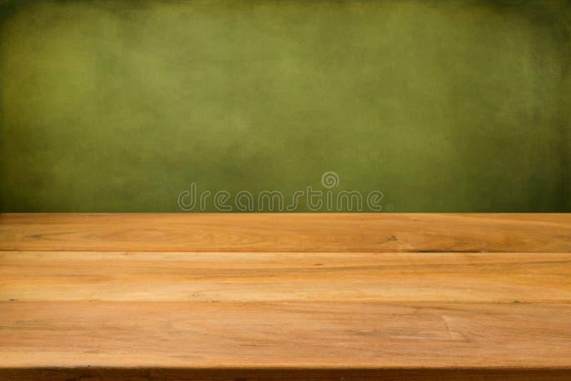 Tabela de madeira vazia sobre o fundo do verde do grunge. imagem de stock