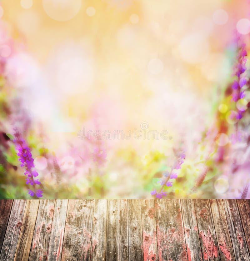 Tabela de madeira velha sobre as flores roxas cor-de-rosa coloridas borradas fotografia de stock