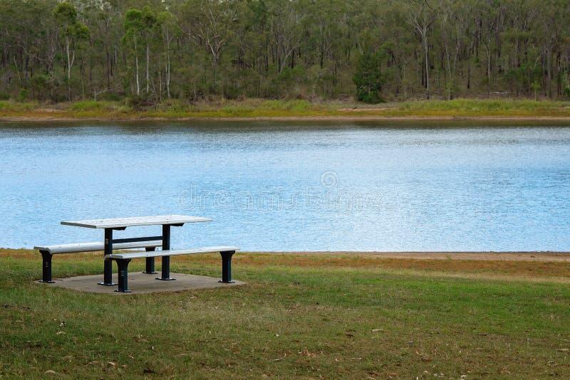 Tabela de piquenique ao lado de um lago foto de stock royalty free
