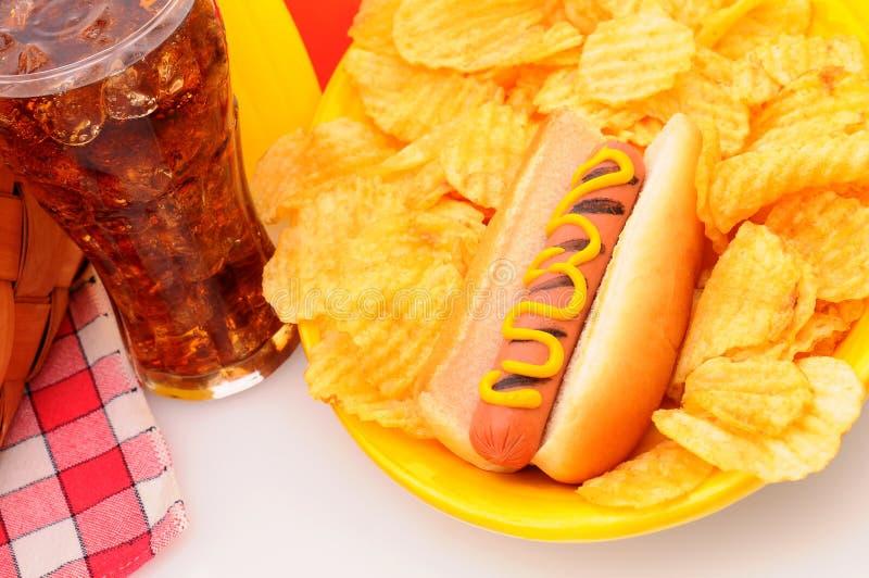 A tabela de piquenique do close up com cão quente lasca a soda fotos de stock royalty free