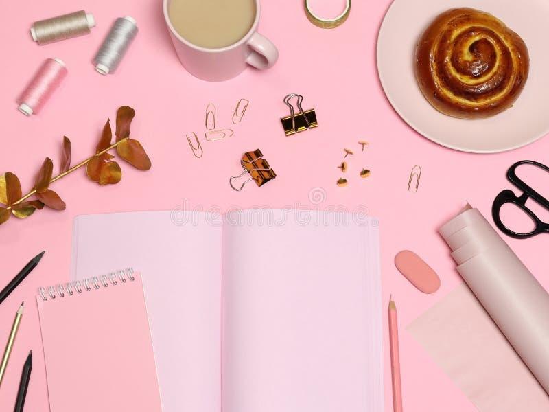 Tabela de trabalho cor-de-rosa com papel de notas, acessórios do escritório, café, cozimento fotografia de stock